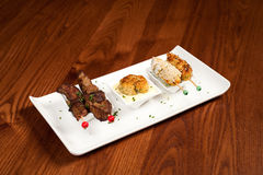 Steak fish & chicken. A tapas plate with steak, fish cake and chicken Royalty Free Stock Photos
