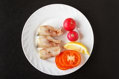 Steak fish with red radish, slice lemon and chopped tomatoes on white plate. Black background. Top view.  Stock Images