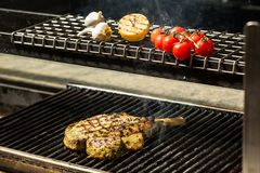 Steak flame broiled on a barbecue. With vegetables. shallow depth of field royalty free stock image