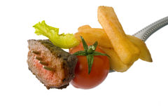Steak on fork. Steak, franch fries, cherry tomato and lettuce on fork isolated on white Royalty Free Stock Images