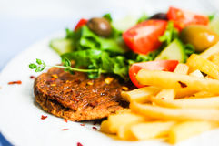 Steak with french fries and salad Stock Images