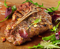 Steak with Fresh Herbs on  rustic wooden board Royalty Free Stock Photography