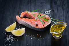 Steak of fresh salmon with aromatic herbs and spices on a dark b Stock Photo
