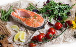 Steak of fresh salmon on crushed brown paper with garnish Stock Images