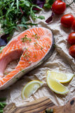 Steak of fresh salmon on crushed brown paper with garnish Royalty Free Stock Photos
