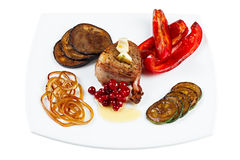 Steak fried in bacon with vegetables on a plate. Royalty Free Stock Images
