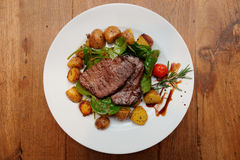 Steak with fried potatoes on wooden table Stock Image