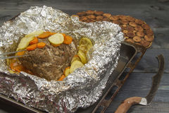Steak fried with vegetables in foil. Steak fried with vegetables and spices in foil on a table Stock Image