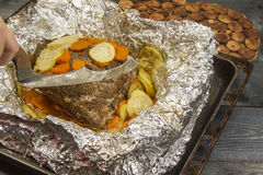 Steak fried with vegetables in foil. Steak fried with vegetables and spices in foil on a table Royalty Free Stock Photography