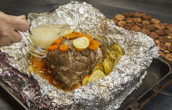 Steak fried with vegetables in foil. Steak fried with vegetables and spices in foil on a table Royalty Free Stock Image