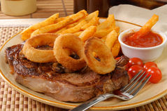 Steak with fries and onion rings Stock Photo