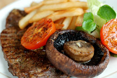Steak with fries and salad. Steak with fries, mushroom, grilled tomato and salad Royalty Free Stock Image