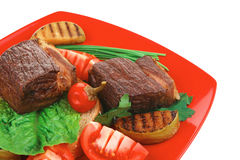 Steak garnished with apples and fresh tomatoes Royalty Free Stock Photos