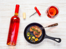 Steak with Glass and Bottle Rose Wine. Glass and Bottle of Rose Wine with Frying Pan and Steak Royalty Free Stock Photography
