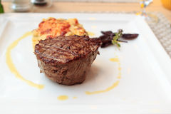 Steak with gratin on a plate Royalty Free Stock Photo