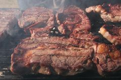 Steak on the Grill. A slice of prime beef on a smoking grill of a Saturday afternoon picnic with the family Royalty Free Stock Photography