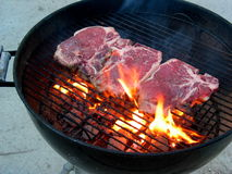 Steak on Grill. Grilling the T-Bone Steak, with flame and charcoal, just placed, rare Royalty Free Stock Photo