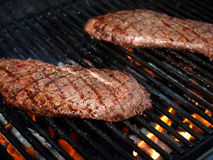 Steak On Grill. Two flat iron steaks cooking on a grill Royalty Free Stock Photography