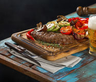 Steak grill with grilled vegetables and light beer. Steak grill with grilled vegetables on the wooden table with light beer Royalty Free Stock Photo