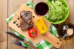 Steak with grilled corn, salad and red wine Stock Photo