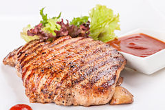 Steak grilled on the plate with garnish of vegetables and sauce. Royalty Free Stock Image