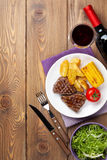 Steak with grilled potato, corn, salad and red wine. Over wooden table. Top view with copy space royalty free stock photo