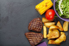 Steak with grilled potato, corn, salad and tomato Stock Image