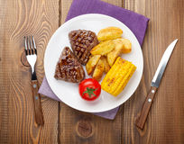 Steak with grilled potato, corn and salad on wooden table Stock Photography