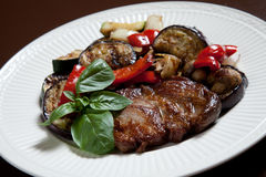 Steak with grilled vegatables. Steak with grilled vegetables and mushrooms on a white plate decorated with basil leafs Stock Image