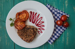 Steak grilled with vegetables and berry sauce on a white plate. Turquoise wooden background. Top view Stock Image