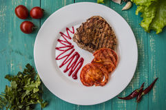 Steak grilled with vegetables and berry sauce on a white plate. Turquoise wooden background. Top view Royalty Free Stock Photos