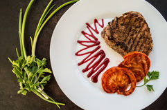 Steak grilled with vegetables and berry sauce on a white plate. wooden background. Top view Royalty Free Stock Photo