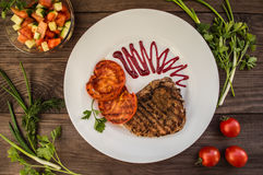 Steak grilled with vegetables and berry sauce on a white plate. wooden background. Top view Royalty Free Stock Images