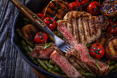 Steak with grilled vegetables in a frying pan. Royalty Free Stock Image