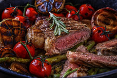 Steak with grilled vegetables in a frying pan. Royalty Free Stock Photos