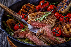 Steak with grilled vegetables in a frying pan. Stock Photography