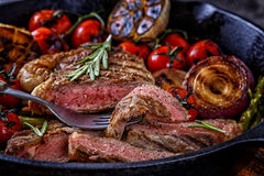 Steak with grilled vegetables in a frying pan. Stock Image