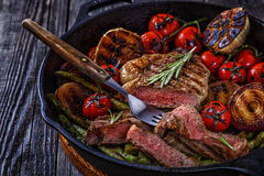 Steak with grilled vegetables in a frying pan. Stock Photos