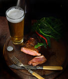 Steak with herbs, hot peppers, cold frothy beer in a glass, vintage knife and fork on a wooden background. Steak with herbs and beer on a wooden background Royalty Free Stock Photos