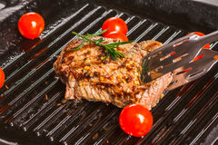 Steak holding forceps and cherry tomatoes Stock Photos