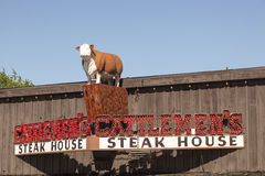 Steak House Cattlemen's in Fort Worth, TX, USA. FORT WORTH, USA - APR 6: Exterior of the Cattlemen's Steak House with a cow statue on top of the building. April royalty free stock images