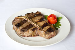 Steak. Juicy steak with vegetables on white plate stock image