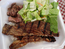Steak, Kalbi, Side salad and white rice in a styrofoam plate Royalty Free Stock Images