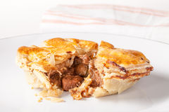 Steak and Kidney Pie. Pie on a plate. Cooked pie with brown pastry. Cut open to show meat filling of steak and kidney Stock Image