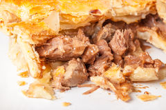 Steak and Kidney Pie. Pie on a plate. Cooked pie with brown pastry. Cut open to show meat filling of steak and kidney. Close up version of filling Royalty Free Stock Photography