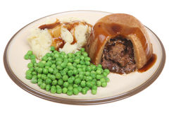Steak & Kidney Pudding. Steak & kidney pudding in suet pastry with mash, peas and gravy Royalty Free Stock Images