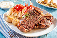 Steak and lobster meal with side dishes