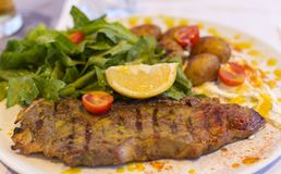 Steak meat grilled with lemon and lettuce. On plate Stock Image