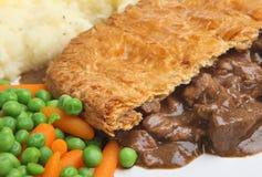 Steak Meat Pie & Mash Dinner. Steak pie with mashed potato carrots & peas Royalty Free Stock Photo