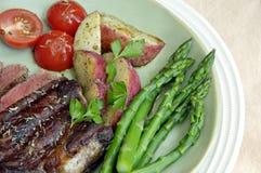 Steak mit Kartoffeln, Tomaten und Spargel stockfotografie